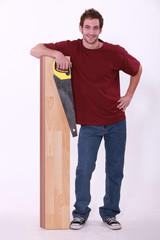 Man stood with laminate flooring and saw