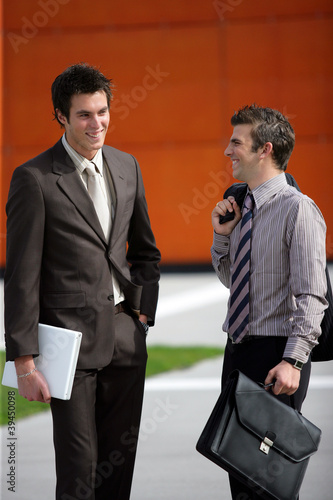 Two young businessmen sharing a joke