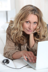 mature woman relaxing on the couch with her laptop