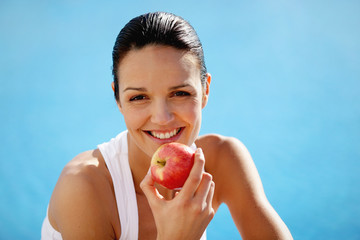 Cheerful woman eating an apple