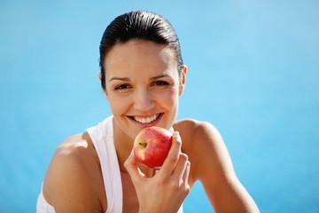 Cheerful woman eating an apple