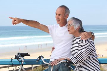 Senior couple having bike ride at the beach