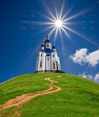 christian church on a green hill under a sparkle sun