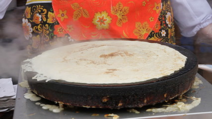 Women prepare pancakes in the street