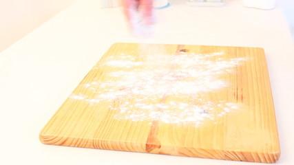 Female hands strew a flour on chopping board