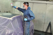 Worker painting a car roof in a paint booth.