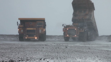 Heavy mining dump trucks unload ore