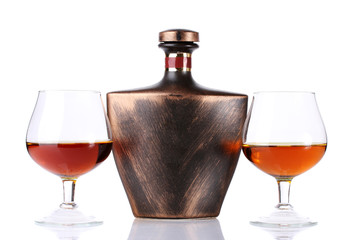 Glasses of brandy and bottle isolated on white