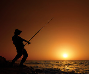 Young fisherman fishing with sunset in the background