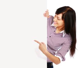 Portrait of a happy teenage girl showing an empty billboard