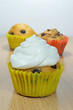 A chocolate chip muffin with fresh cream on top