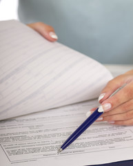 Close-up of a businesswoman hand with a pen over paper
