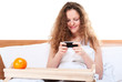 Woman plays video games on mobile phone in bed