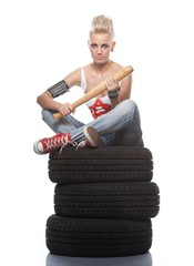 Punk girl sitting on a tires.