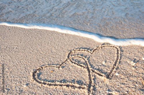 2 gemalte Herzen am Meer in der Brandung