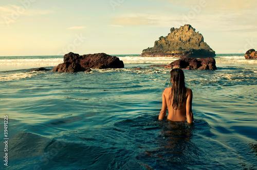 Chica sentada en la orilla del mar