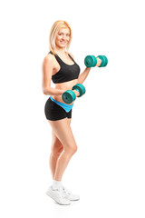 Full length portrait of an attractive woman lifting up weights