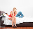 Upset woman sitting on a bed while her boyfriend is sleeping