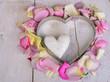 Herz aus Rosenblütenblättern mit kleinem Marmorherz