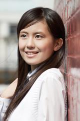 壁にもたれて微笑む女子高校生