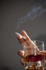 酒とタバコを持つ男性の手元