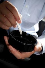 タバコをもみ消す男性の手元