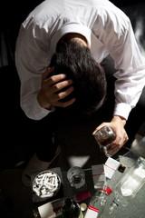 酒を飲んで頭を抱える男性