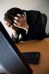 PCの前で頭を抱えるビジネスマン