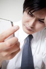 スマートフォンを持って悩むビジネスマン