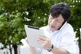 電話しながらタブレットPC操作するビジネスマン