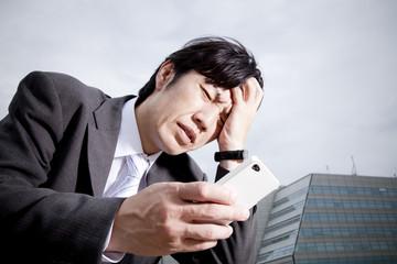 スマートフォンを見て頭を抱えるビジネスマン