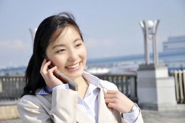 携帯電話で話すOL