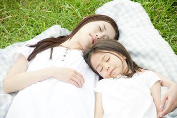 草原で寝る女性と女の子