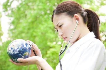地球儀に聴診器を当てる看護師