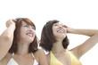 空を見上げて微笑む水着姿の女性2人