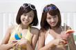カクテルを持ち微笑む水着姿の女性2人