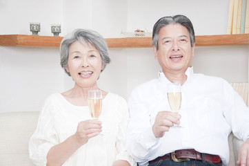 シャンパングラスを持って微笑むシニアカップル