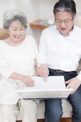 ノートパソコンを見る笑顔のシニアカップル