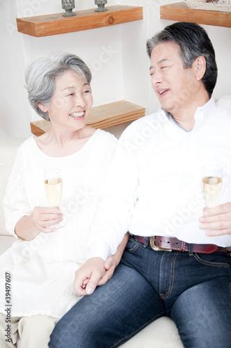 シャンパングラスを持って見つめ合うシニアカップル