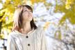イチョウの並木道を歩く笑顔の女性