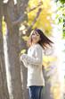 イチョウの葉を持ち振り返る笑顔の女性