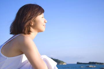 海辺で遠くを見つめる女性