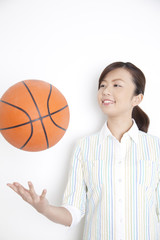 バスケットボールを片手で放り上げる女性