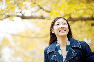 銀杏を見上げながら歩く女性