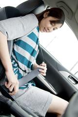 車の助手席でシートベルトを締める女性