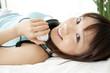 ベッドで寝転んで微笑む女性