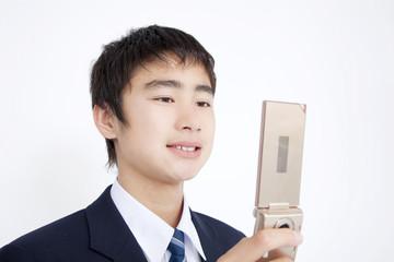 携帯電話のメールを確認している男子中学生