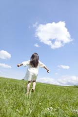 草原を歩く女の子の後ろ姿