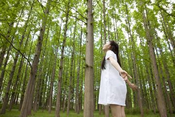 林の中で両手を広げる女性