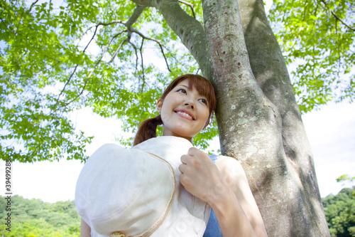 木にもたれて微笑む女性